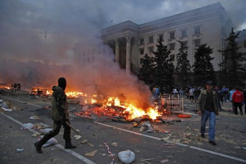 A protester walks past a burning pro-Russian tent camp near the trade union building in Odessa May 2, 2014. At least 38 people were killed in a fire on Friday in the trade union building in the centre of Ukraine's southern port city of Odessa, regional police said. REUTERS/Yevgeny Volokin (UKRAINE - Tags: POLITICS CIVIL UNREST TPX IMAGES OF THE DAY)